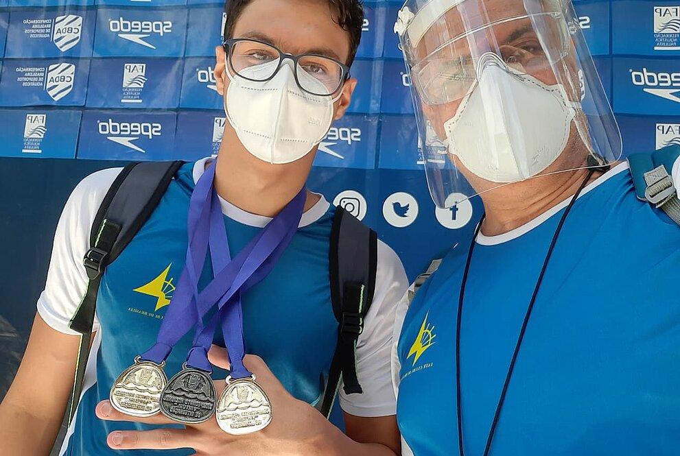 Rapaz com máscara exibe medalhas conquistadas em competições ao lado de um homem com proteções faciais