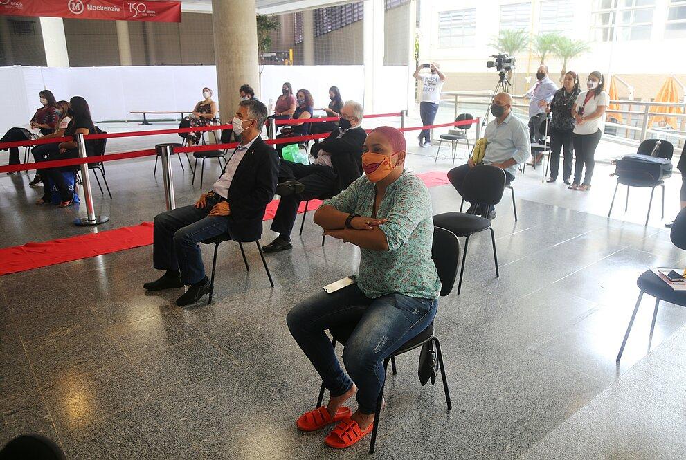pessoas sentadas em cadeiras em um espaço aberto acompanham apresentações