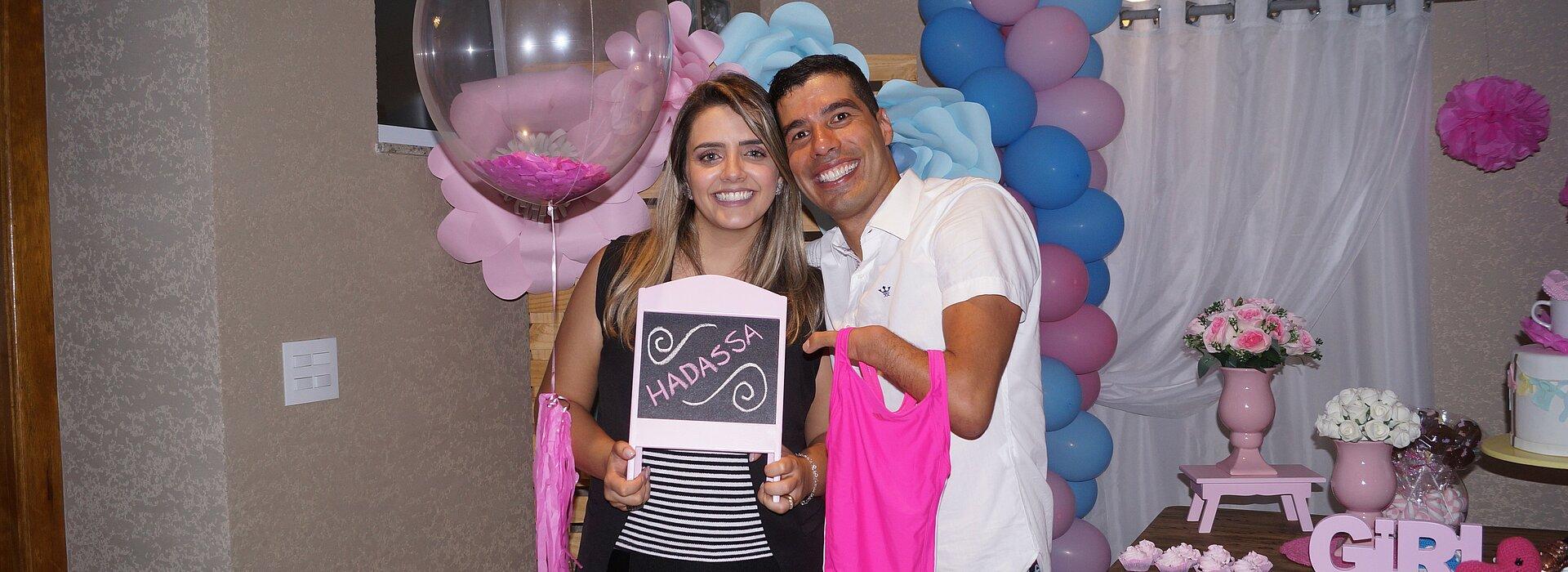 Daniel Dias e sua esposa Raquel Andrade segurando lousinha com o nome da filha