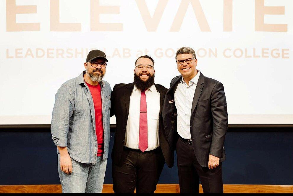 Professor Anderson posando para foto ao lado de dois representantes do Gordon College em evento do Elevate.