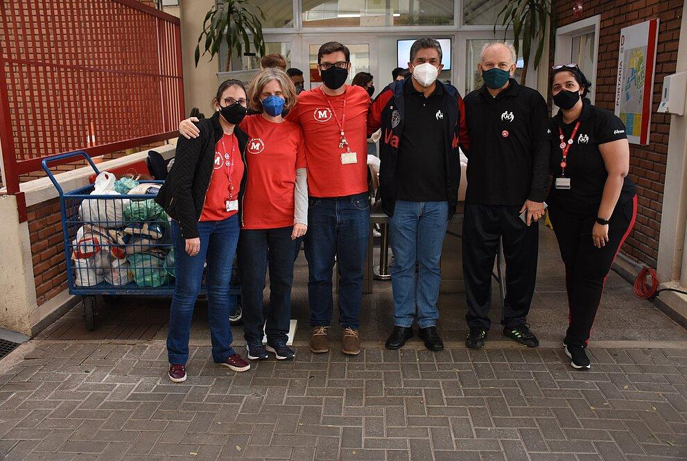 Seis pessoas de máscara posam para foto em frente a entrada do campus Higienópolis do Mackenzie