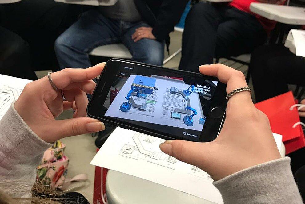 aluna segurando celular em frente a uma folha de planta com modelo 3D no celular