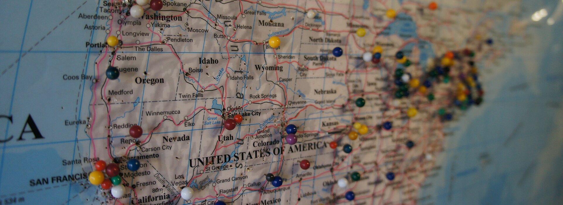 Foto mostra o mapa dos Estados Unidos com vários alfinetes redondos coloridos.