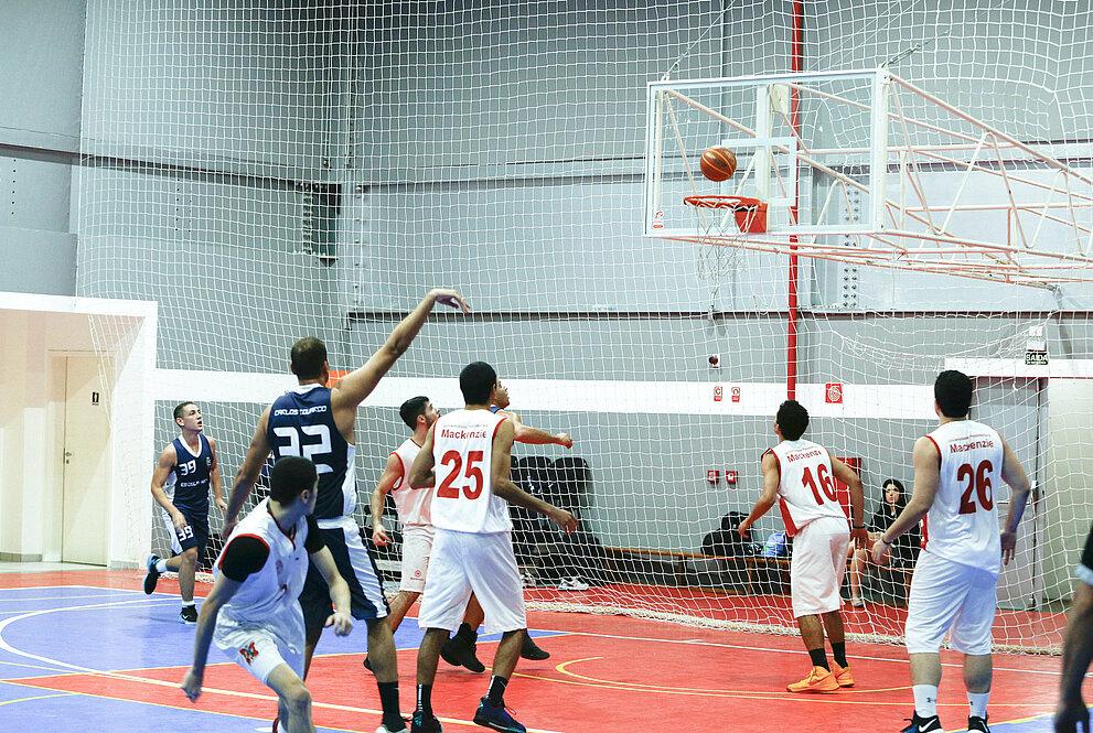Arremesso pela Escola Naval, com atletas mackenzistas ao redor, olhando a bola indo em direção à rede de basquete.