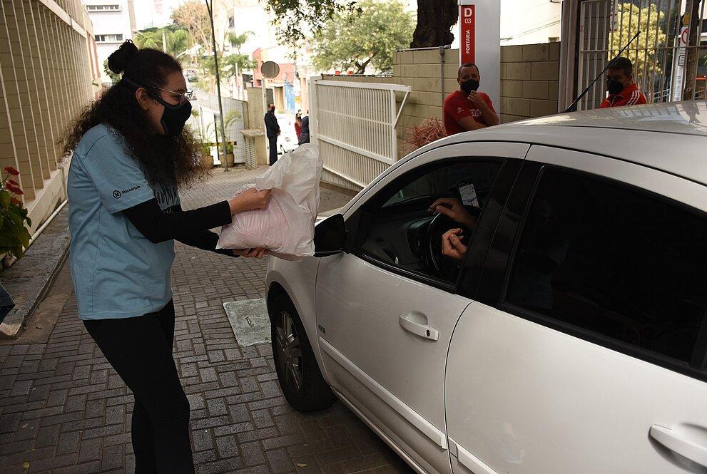 mulher de camiseta azul coleta doação de motorista dirigindo carro branco