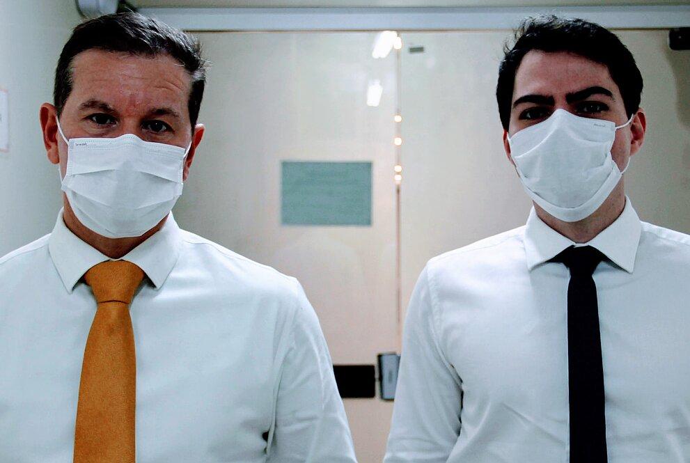 Dois médicos com camisa, gravata e máscara estão no corredor de um hospital com paredes claras