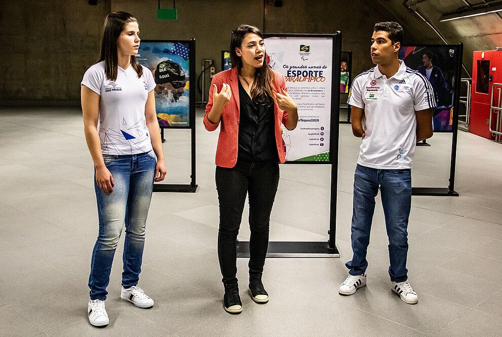 Alana Maldonado ao lado de Cinthia do Carmo e Daniel Dias em meio aos painéis da exposição