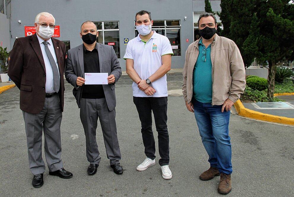 Quatro homens, de pé, posam para foto em frente ao Hospital