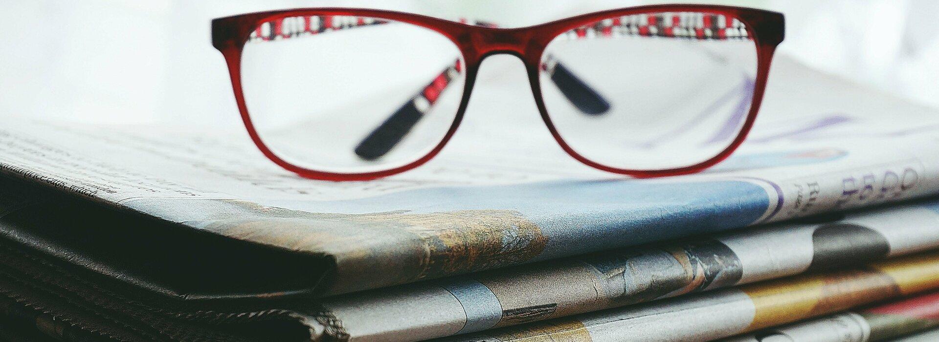 óculos em cima de vários jornais