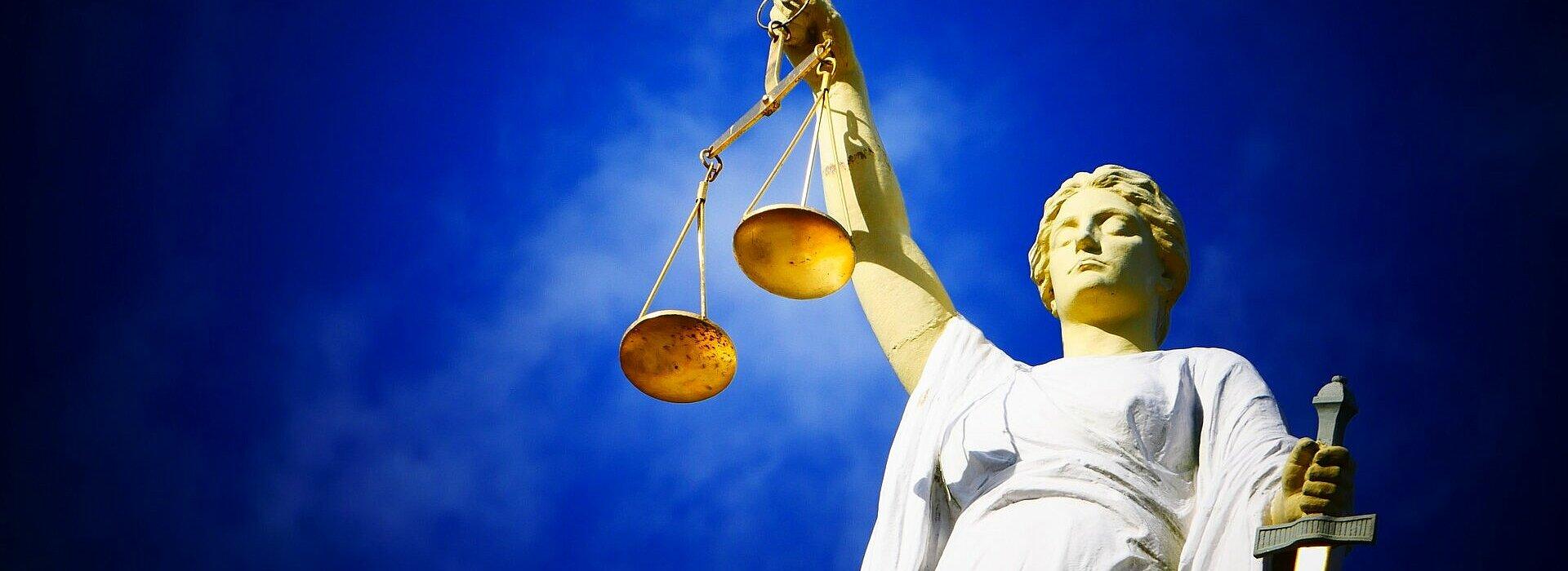 Imagem de uma estátua segurando uma balança, objeto símbolo do julgamento.