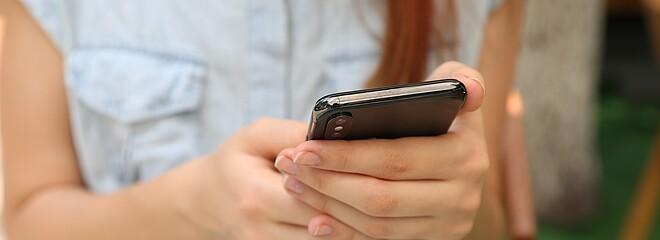 A foto mostra uma mulher com cabelo comprido mexendo no celular. Seu rosto não aparece, apenas seus braços e as mãos segurando o celular.