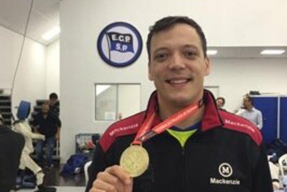 Nicolas Silva sorrindo e segurando uma medalha de ouro