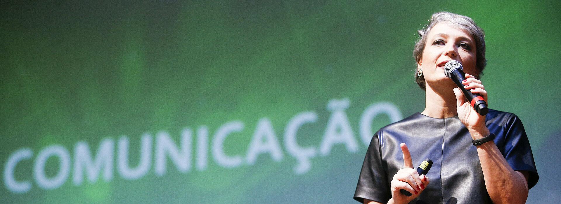 Daniela Cachich no palco com telão ao fundo