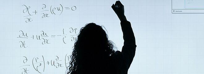 Mulher de cabelos longos, de costas, escreve equações em uma lousa branca
