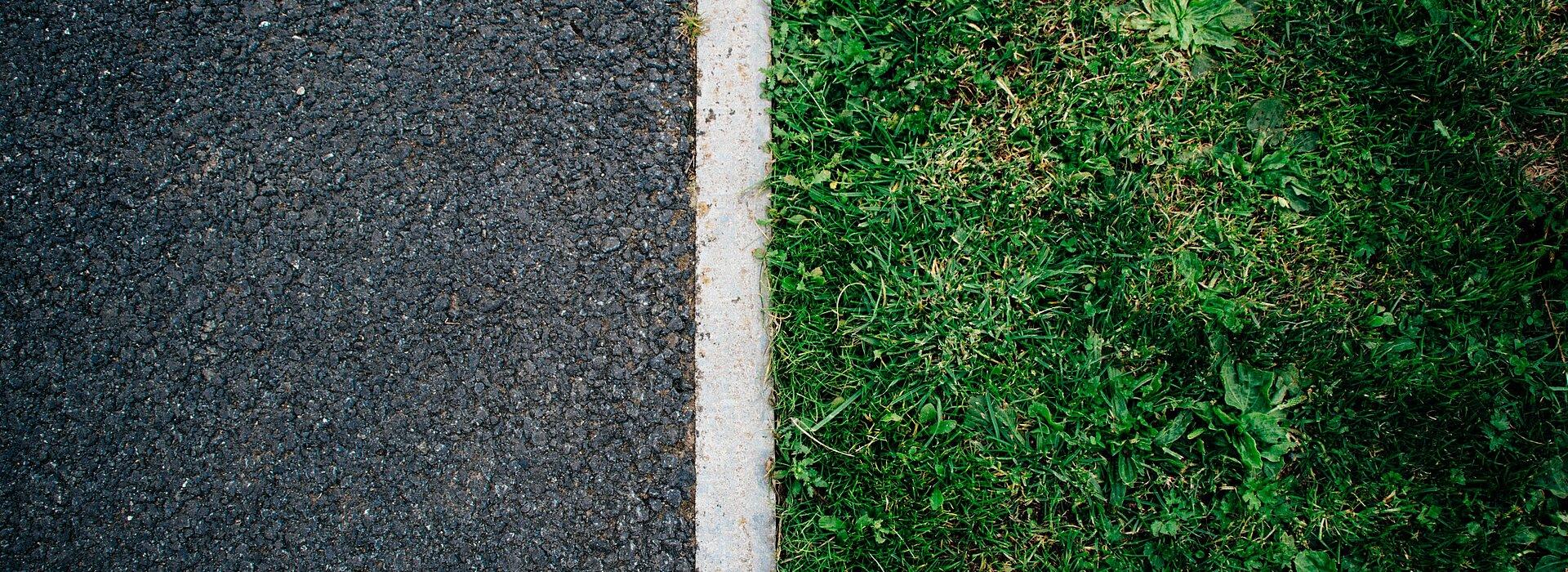 Do lado esquerdo, o asfalto. Do lado direito, a grama. Uma linha branca separa os dois.
