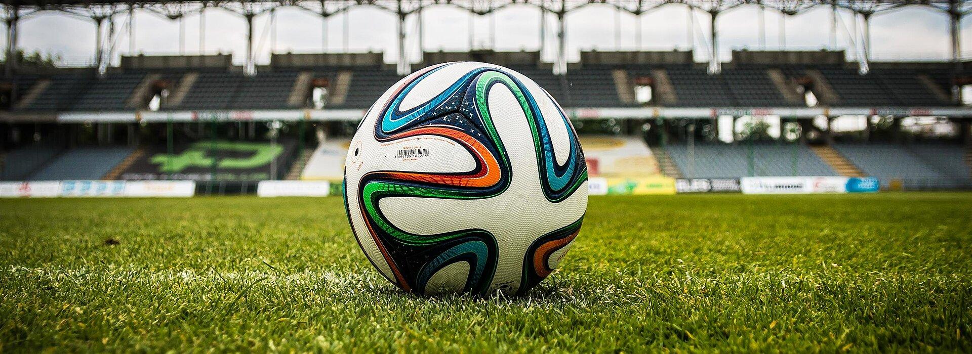A foto mostra uma bola no meio de campo de futebol