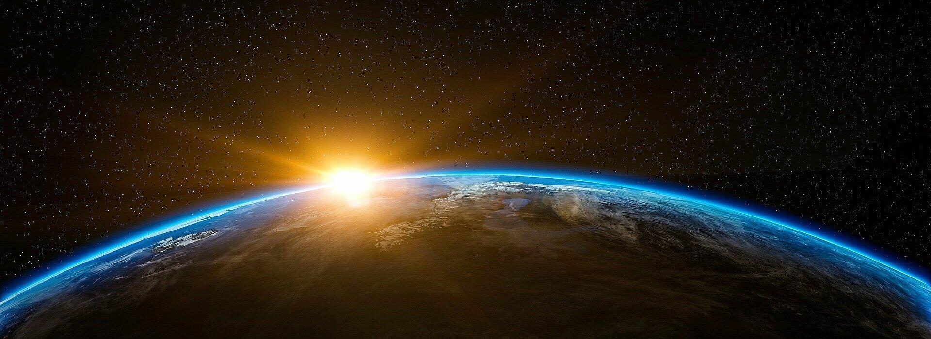 Planeta Terra visto de longe, com Sol ao fundo.