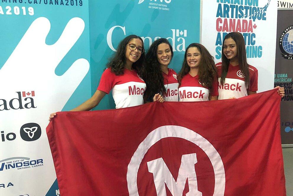 Quatro meninas seguram bandeira com o símbolo do Mackenzie