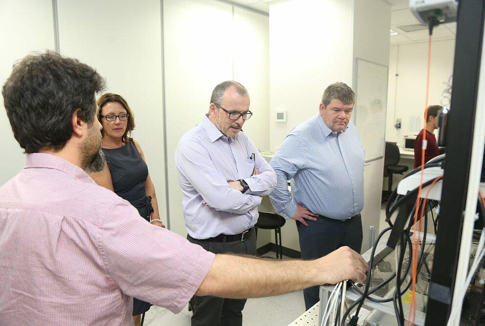 Quatro pessoas observam equipamento eletrônico no laboratório do Mackenzie