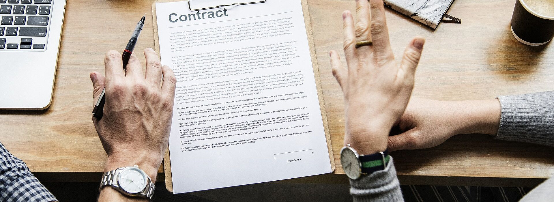 """pessoas discutindo em uma mesa com computador e papel onde se lê """"contrato"""" em inglês"""