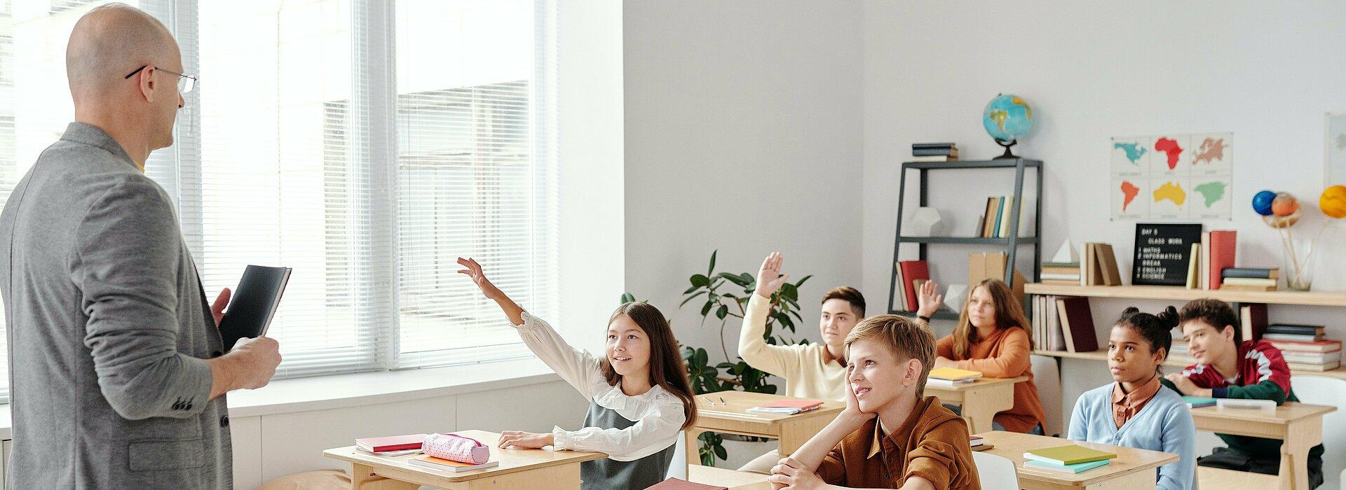 Professor e crianças na sala de aula enpolgadas para aprender