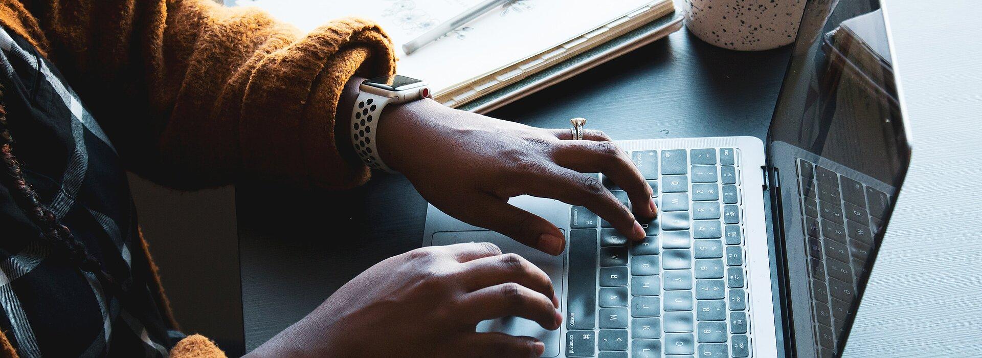 A foto mostra as mãos de uma mulher negra, que usa um relógio, mexendo em um notebook. Ao lado do notebook tem um caderno e uma xícara.
