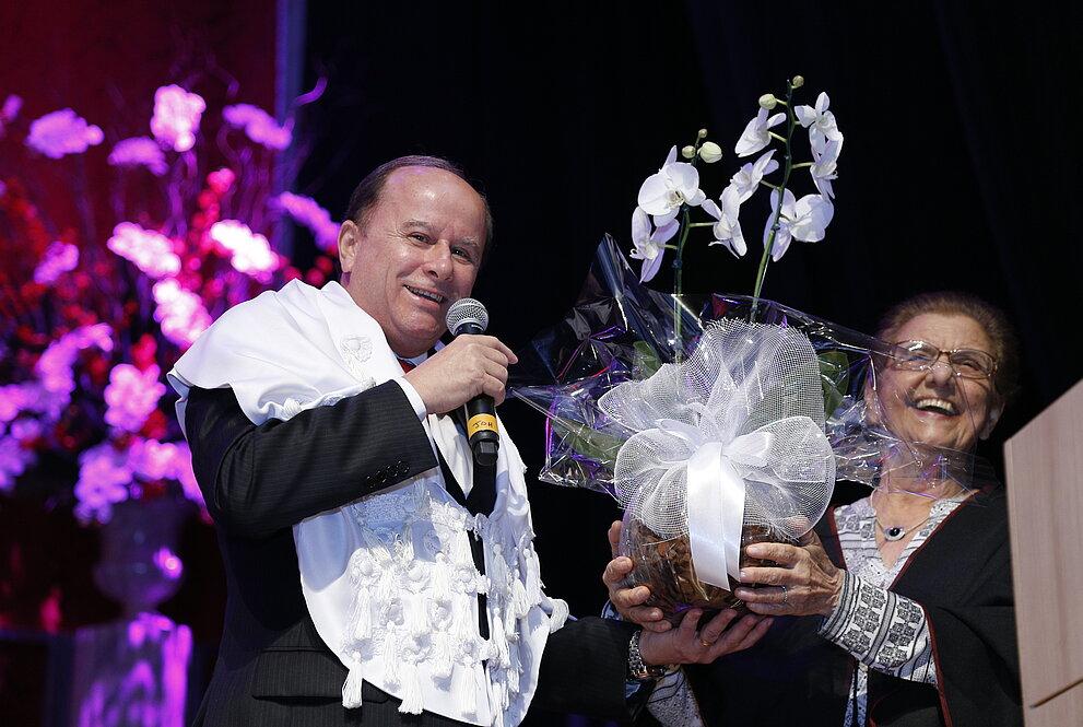 Reitor entrega orquídea à doutoranda, ambos sorrindo.