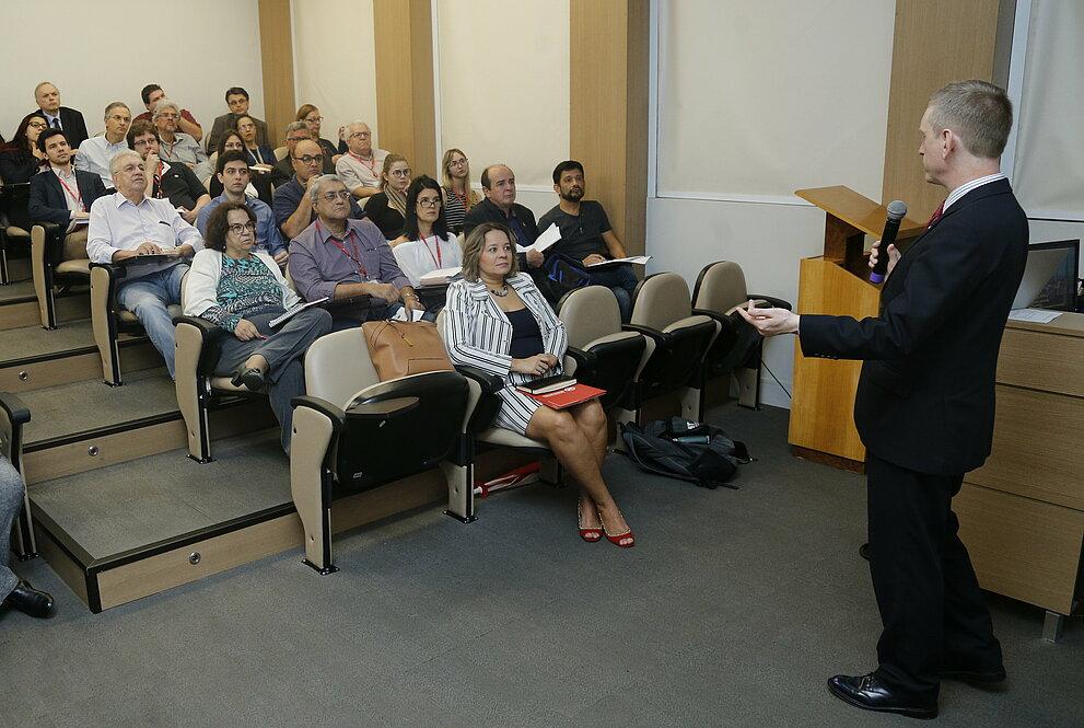 Platéia sentada nas cadeiras, ouvindo o palestrante da Coventry University.