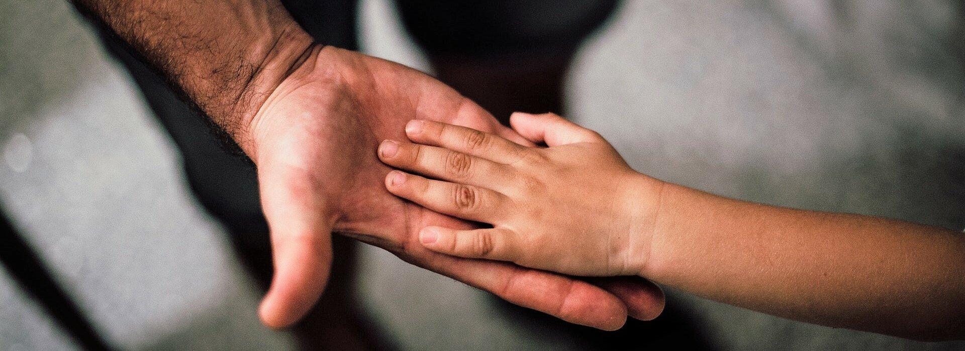 mão masculina de adulto apoia mão de criança numa imagem em close