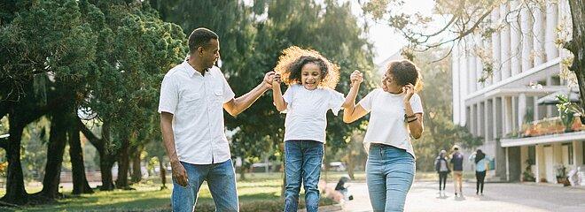 Criança pulando de mãos dadas com os pais