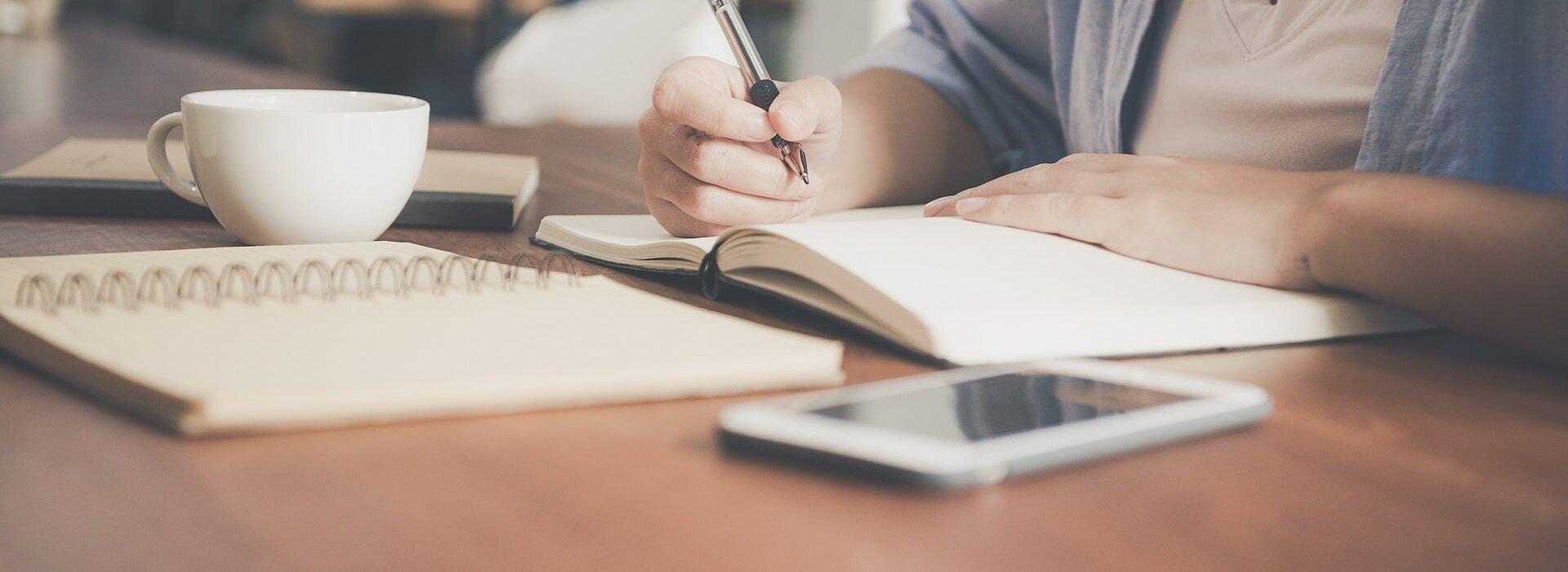 mesa com caderno, tablet e pessoa escrevendo
