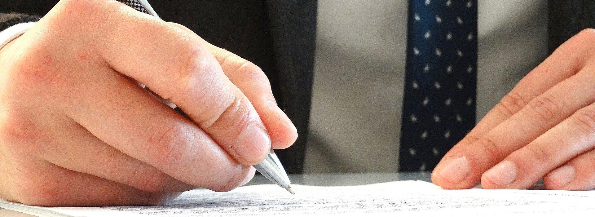 mãos masculinas assinando um documento