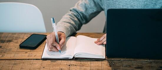 A foto mostra um homem, mas não conseguimos ver seu rosto. Ele está escrevendo em um caderno. Está com um celular do lado e um notebook na sua frente.