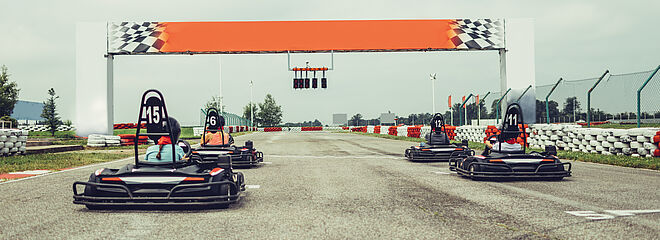 carros de kart posicionados para a largada em uma pista corrida