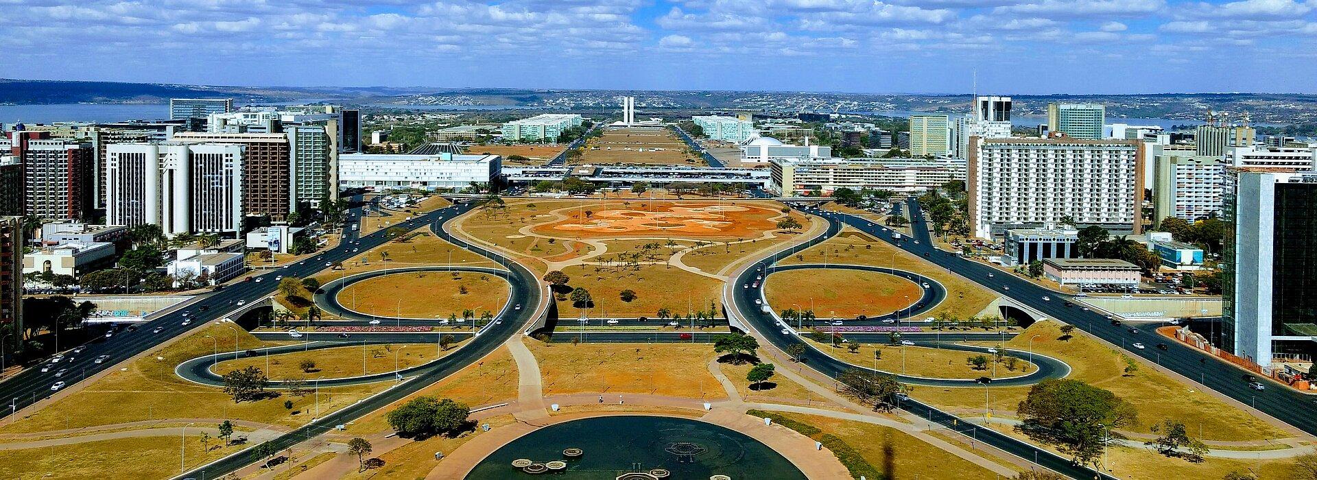imagem do alto do planalto, em Brasília. o céu está azul, com algumas poucas nuvens brancas e pode-se ver os prédios, ruas e praças