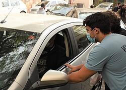 Homem de camiseta azul conversa com motorista de um carro prateado