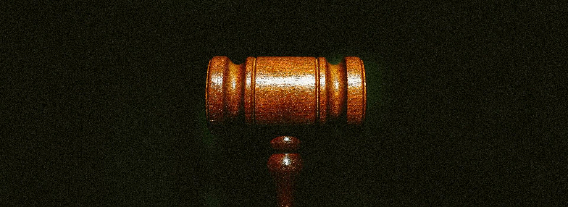 Na foto um malhete marrom, o famoso martelo utilizado pelo juiz, está centralizado no meio. O fundo é todo escuro e o foco está somente no martelo.