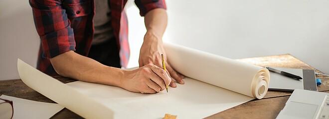 A foto mostra um homem com um lápis na mão começando a desenhar em uma cartolina em branco. Na mesa tem outras folhas e réguas espalhadas. Não conseguimos ver seu rosto.
