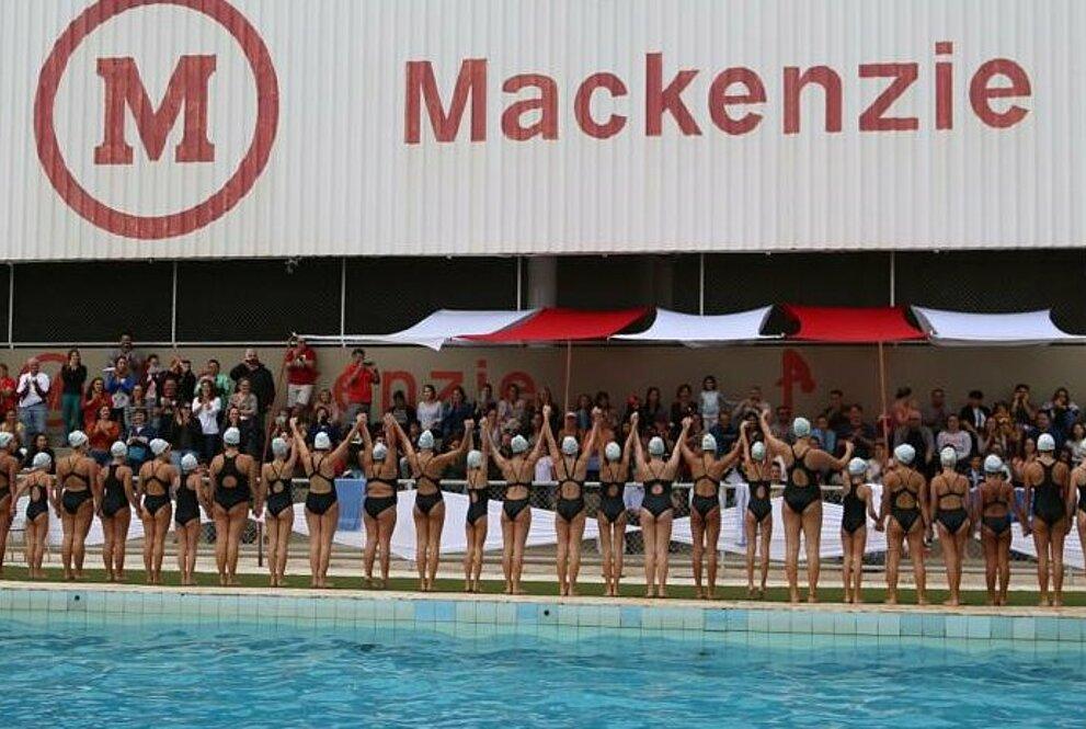 Alunas posicionadas de costas com as mãos para cima em frente a piscina