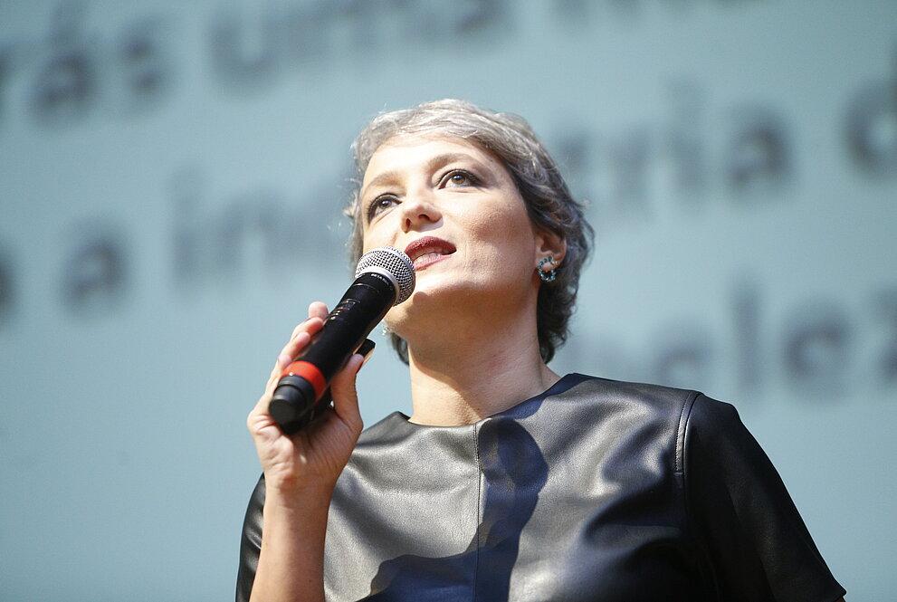 Daniela segurando microfone em frente ao telão do auditório
