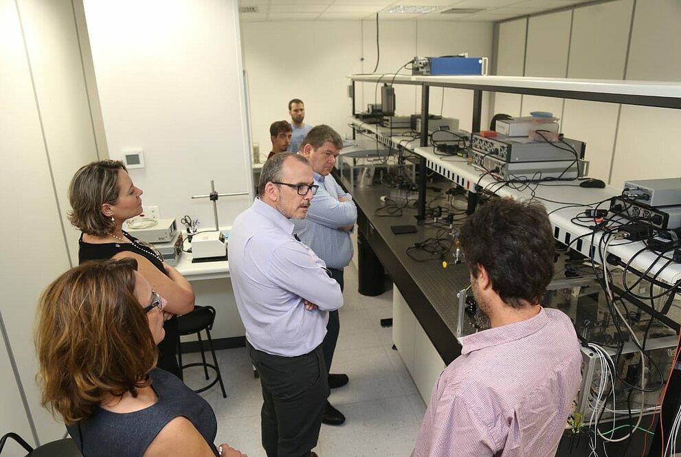 Cinco pessoas observam equipamento eletrônico no laboratório do Mackenzie