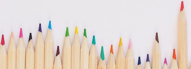 Vários lápis de cor na parede branca