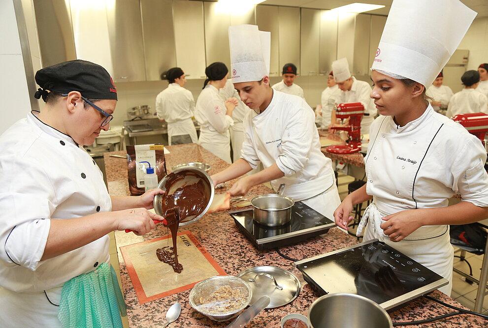 Alunos cozinhando durante a prova.