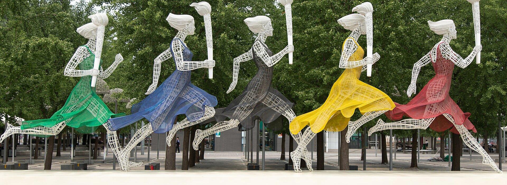 Estátuas de mulheres correndo com a tocha olímpica