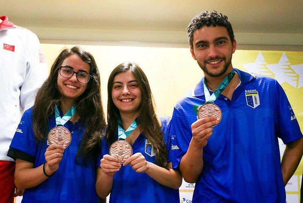 Três atletas de uniforme azul posam para foto com suas medalhas de terceiro lugar
