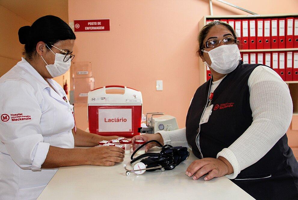 duas mulheres de máscaras e aventais do hospital trabalhando