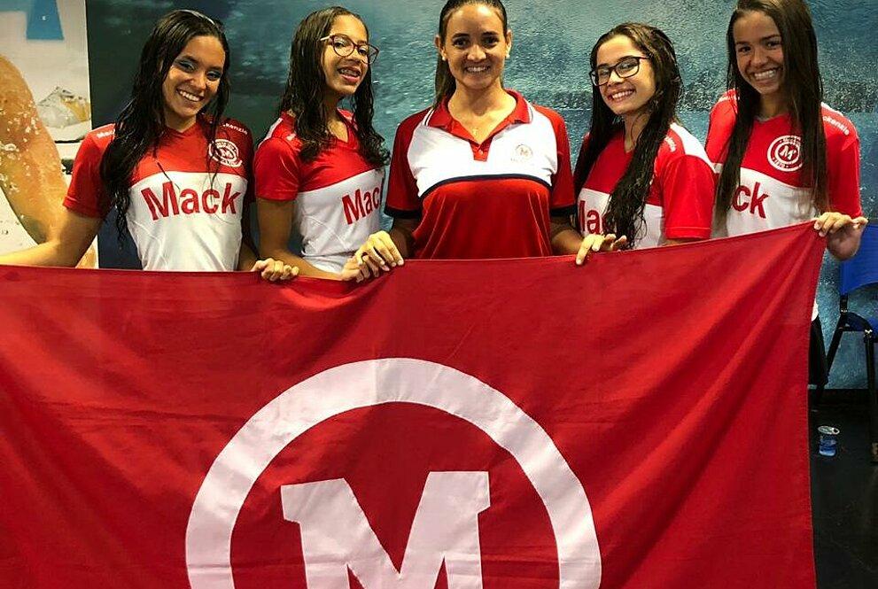 Atletas com treinadora segurando a bandeira do Mackenzie.