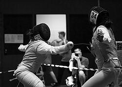 A foto em preto e branco mostra duas esportistas durante o combate de esgrima. Uma está atacando a outra, conseguimos ver bem sua máscara e arma posicionada no corpo da adversária - que está de costas.