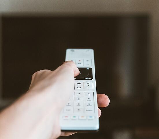 Na imagem a mão de uma pessoa segura um controle branco, mirando diretamente para TV. Somente o controle está focado.