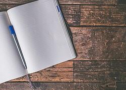 A imagem mostra um caderno em branco, em cima de uma mesa de madeira. No meio do caderno, tem uma ceneta.